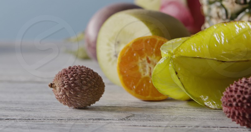 Close-up freshly picked tropical ripe fruits - carambola litchi and passion fruit on a wooden background. Vegetarian healthy concept. Panoramic motion 4K video 3840 2160p. photo