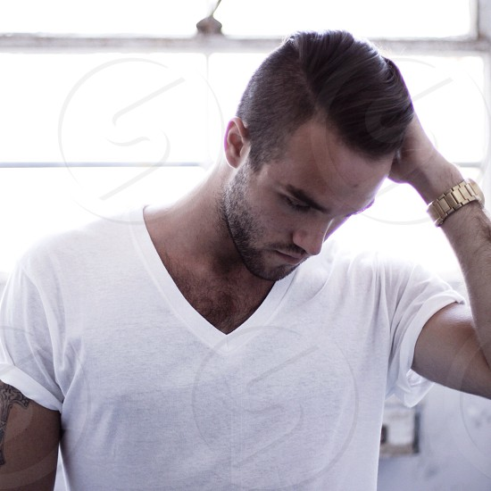 man in white v neck shirt holding his hair photograph photo