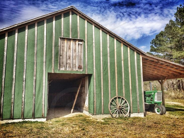 green wooden barn with grey wooden wagon wheel photo