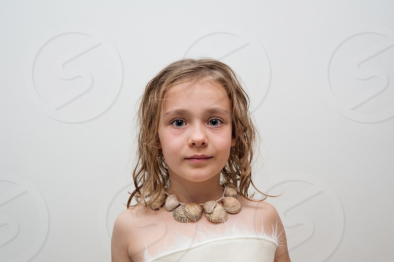 A little girl wearing a sea shells necklace. photo