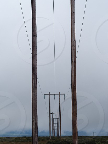 line of electric posts under cloudy sky during daytime photo