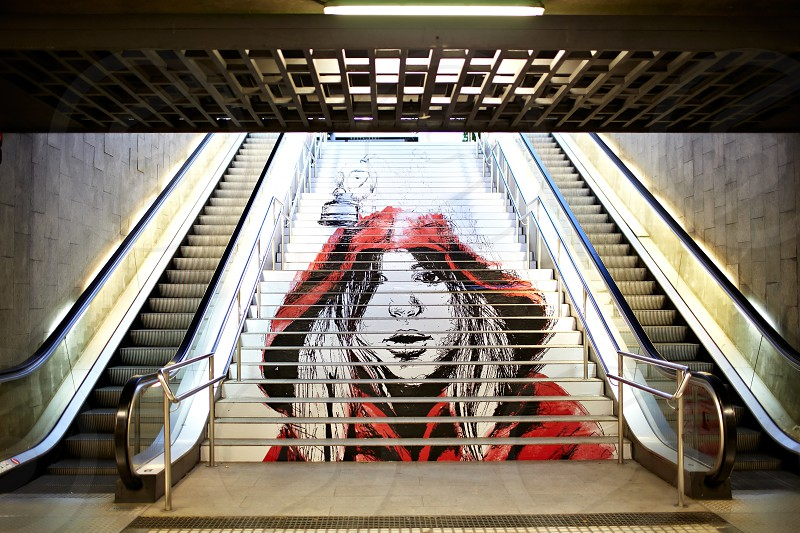 BARCELONA - MAY 23: Graffiti with the picture of a modern girl-teenager in a red loose overall on the steps of the Metro on May 23 2012 in Barcelona Spain. photo