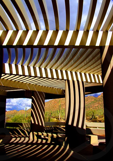 Striped shadows form on the posts and ceiling of a wooden canopy of a desert building. photo