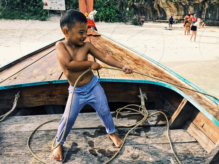 child in blue pants pulling a brown rope on brown wooden jon boat photo
