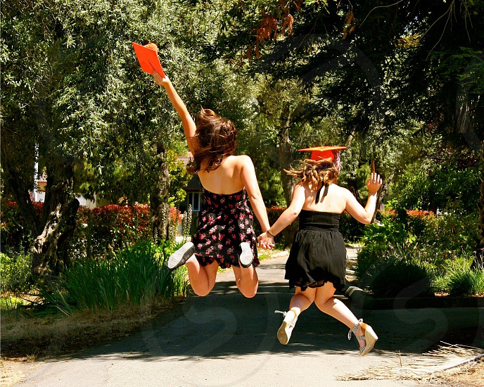 Graduation free caps best friends  celebrating jumping joy holding hands arms up happy  photo