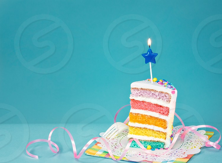 Slice of  birthday cake on a blue background with colorful layers and candle. photo