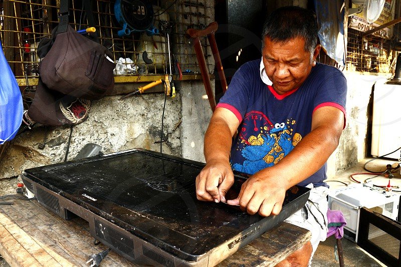 ANTIPOLO CITY PHILIPPINES - MARCH 11 2019: A household appliance repair shop worker fixes an old LCD television. photo