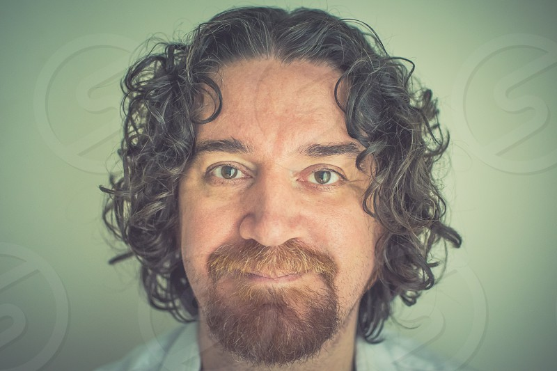 man with black curly hair with brown beard and mustache photo