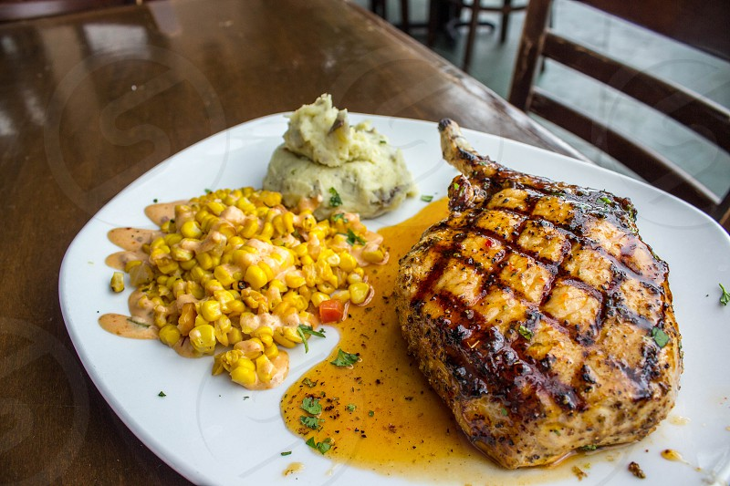 roasted meat beside yellow corn on white ceramic plate photo