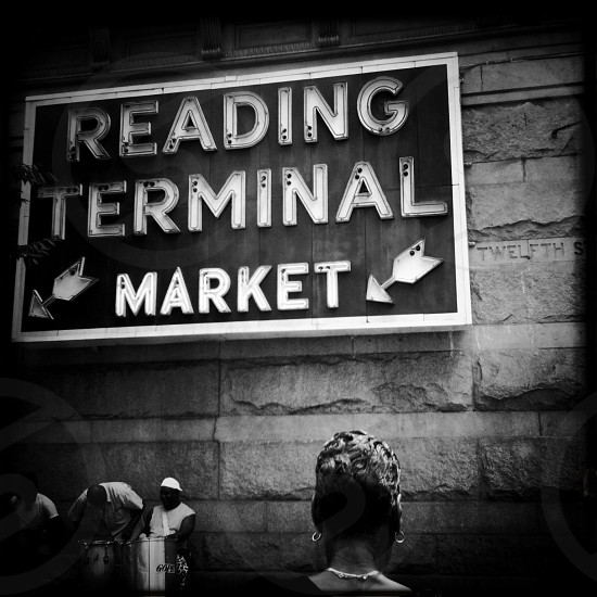 Reading Terminal Market is an enclosed public market located in what was Reading Railroad's train shed. Over one hundred merchants offer fresh produce meats fish groceries ice cream flowers baked goods and local and ethnic foods including Pennsylvania Dutch/Amish specialties. 12th & Arch Streets Center City Philadelphia. Philly market neon sign facade stone black and white B&W street musicians drummer photo