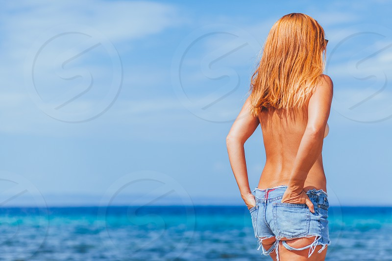Hippie young ginger woman sunbathing topless on a beach photo