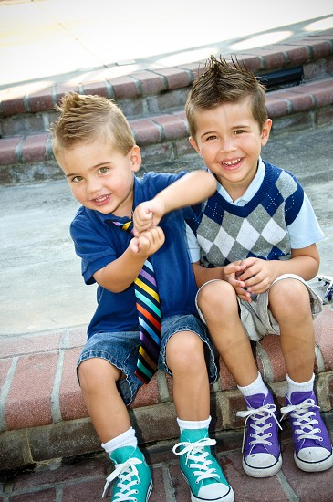 two boys sitting on brown bricked chair photo