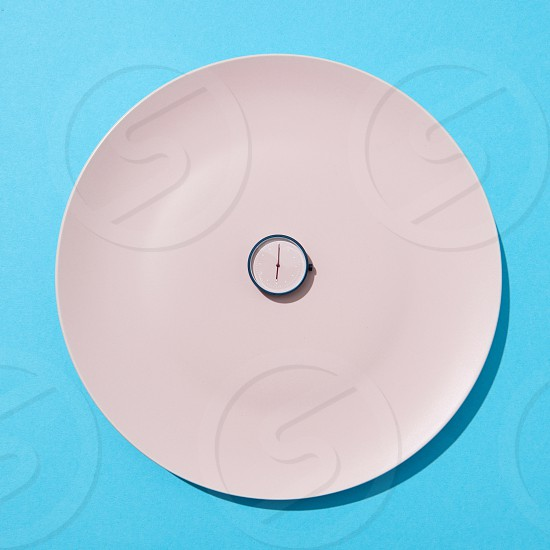 White plate with whatch shows six o'clock on a blue background copy space. Flat lay. Concept of limiting the intake of food diet and weight loss. photo