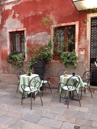 Street restaurant cafe dining tables chairs green linen plants windows  photo