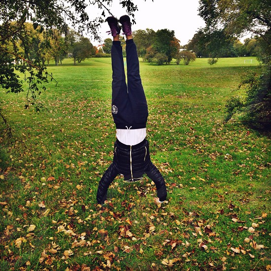 person in black jacket hand stand photo