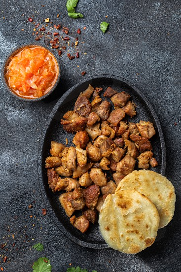 COLOMBIAN FOOD. Fried pork CHICHARRON AREPAS and colombian tomato sauce. Top view. Black background photo