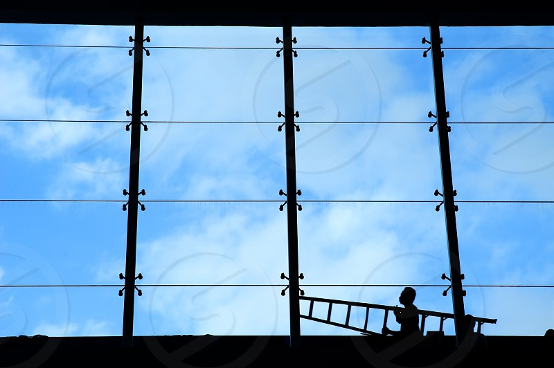 Silhouette of building interior and workman carrying ladder against blue sky. photo