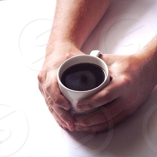 white ceramic mug with black liquid photo