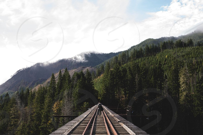 man walking on brown metal rail road tracks photo