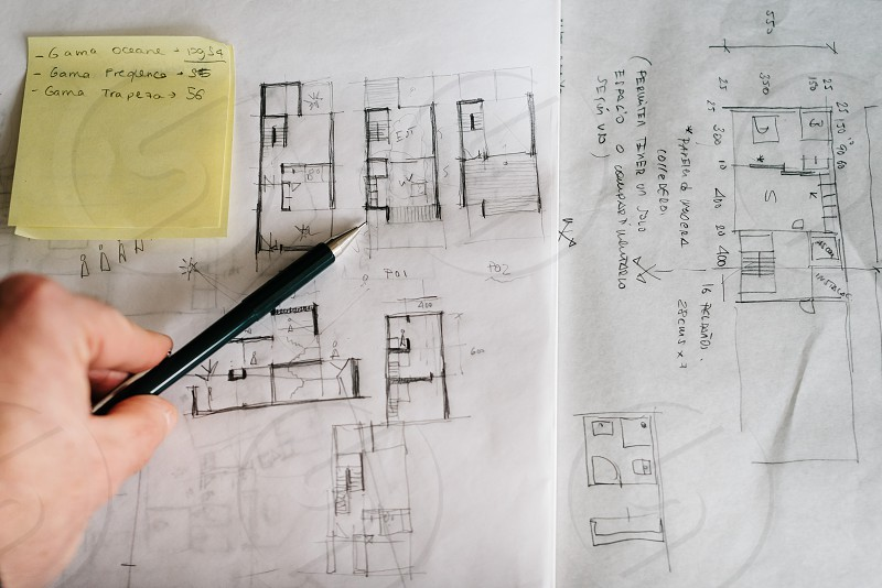 Man architect drawing plan or design by pencil on paper at office desk photo