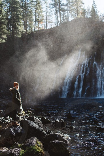 woman with brown hat looking at waterfall photo