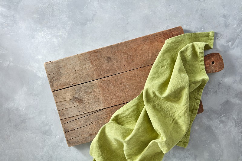 Green kitchen napkin on an old wooden board on a gray concrete background with copy space. Top view photo
