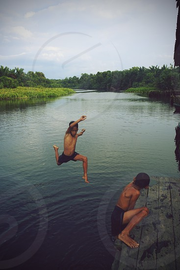 boy jumping on river photo