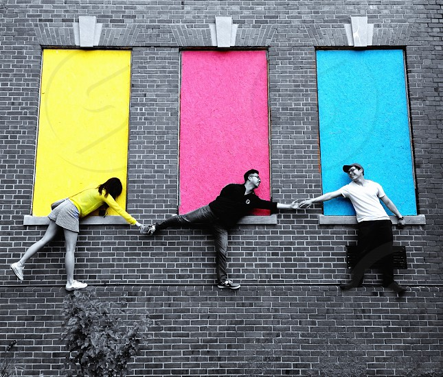 2 men and 1 woman on wall\ photo