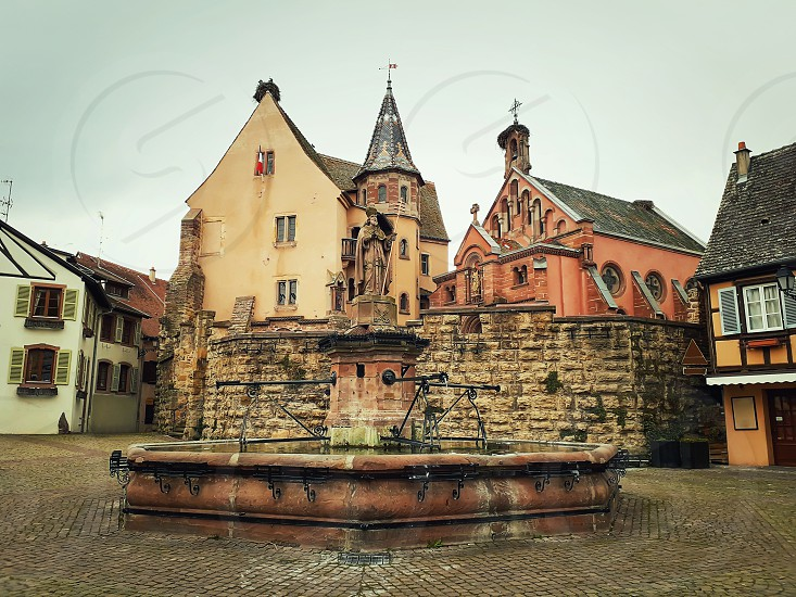 Castle church and fountain named Saint Leon on the central square of Eguisheim village in Alsace France. photo