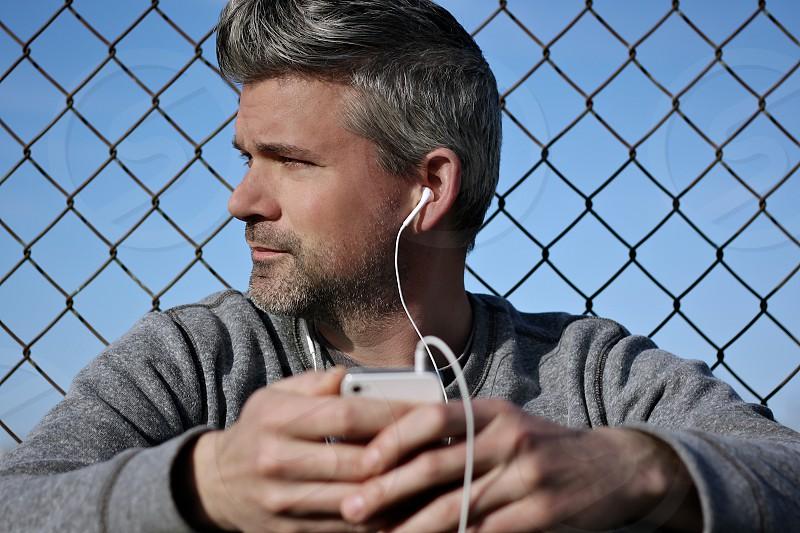 portrait man fence chain link music phone iphone headphones grey hands focus photo