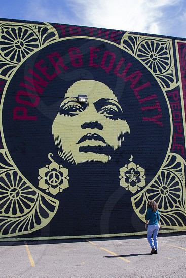 Woman looking toward large wall mural depicting gender and racial empowerment photo