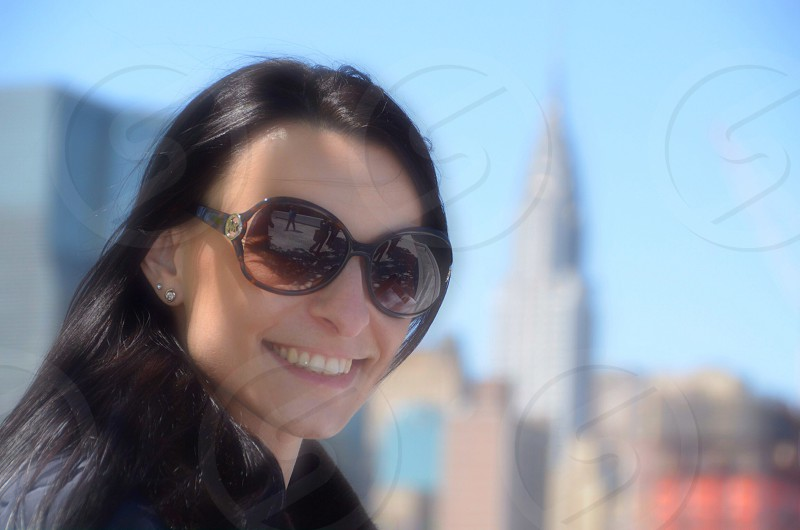 woman in sunglasses standing in front of new york skyline photo