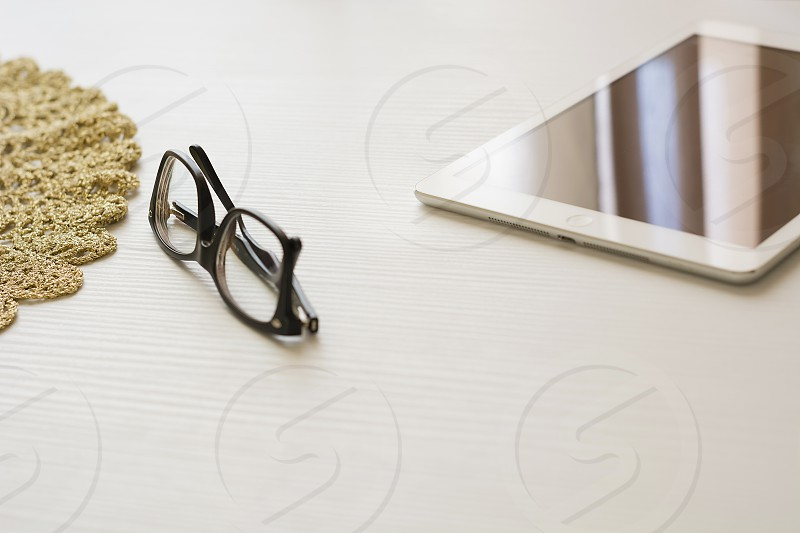 glasses and tablet on a white table photo