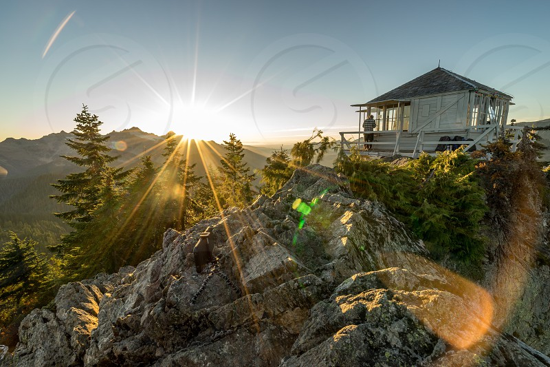 person standing on the patio of wood house on a cliff over rocks and pine trees under the sun photo