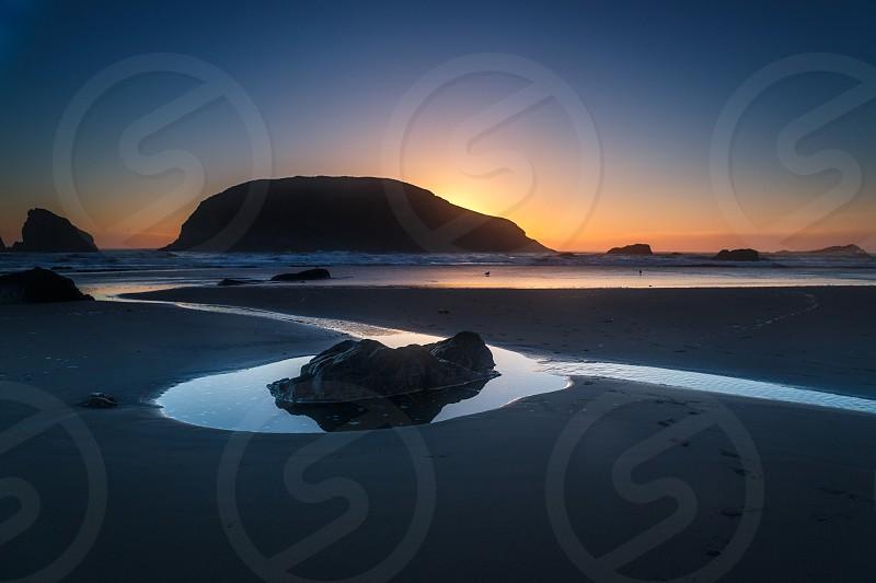 Setting Sun and beach reflections Harris Beach State Park Brookings Oregon. photo