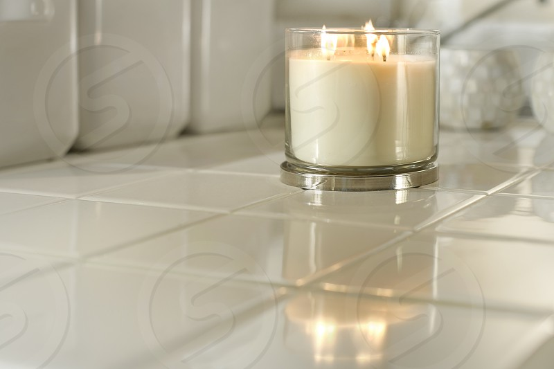A white contemporary jar candle on a white countertop. Fire flame relaxing modern burn three 3 wick glass tile jars chrome home rest. photo