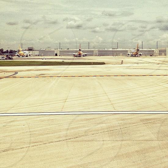 three white passenger airplanes on airport during daytime photo