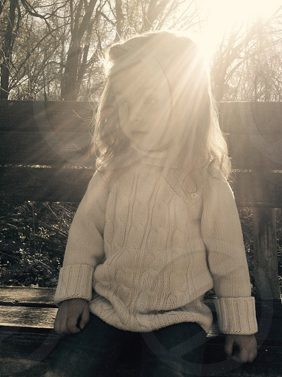 girl in white turtle neck sweater sitting on bench photo