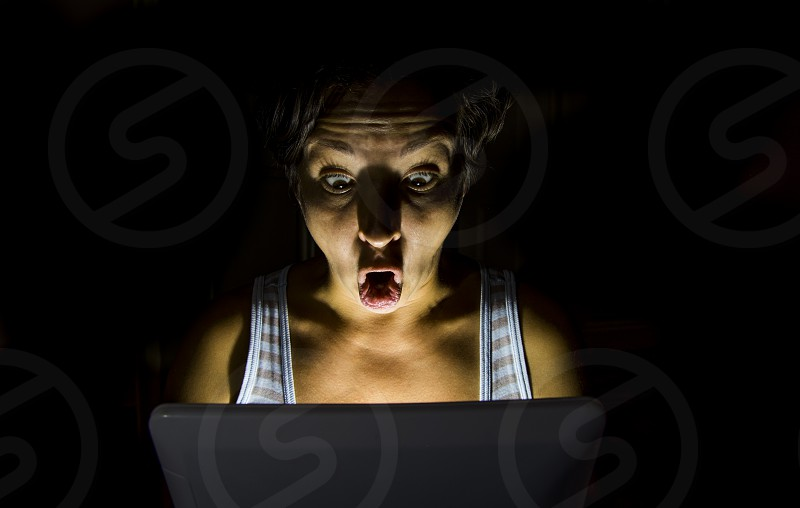 Woman in dark excited by looking in the tablet. photo