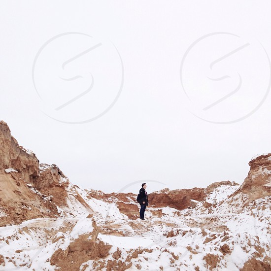 person wearing black jacket on snow covered brown rock formations photo
