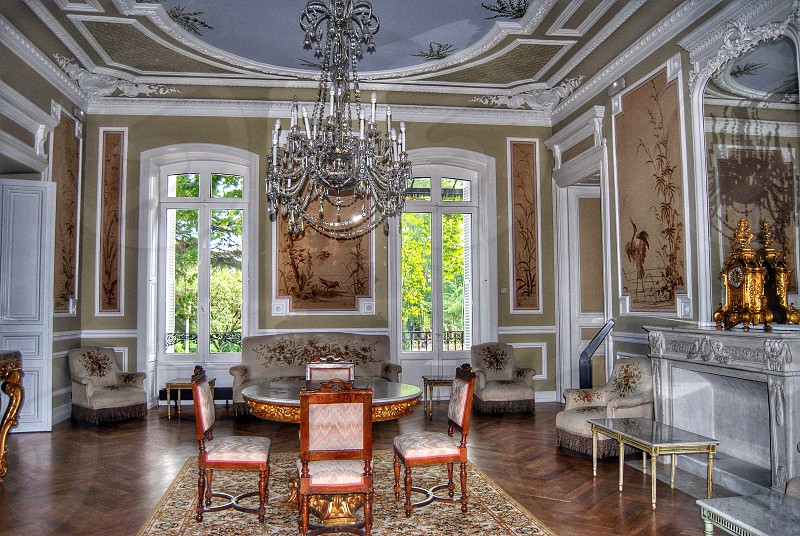 room with chandelier round table and chairs and wall paintings photo