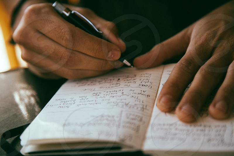 man writing on notebook macro photography photo