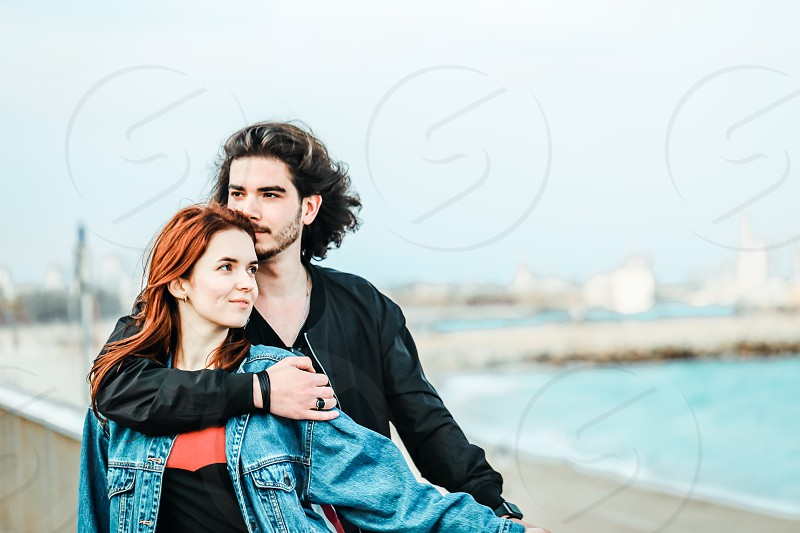 Happy young couple enjoying sea view on a warm spring day. Handsome man gently hugs his beautiful redhead sweetheart. photo