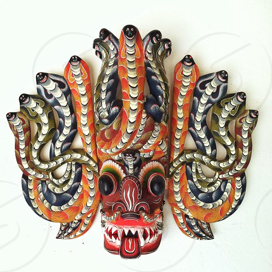 brown blue and orange tribal mask with snake wall decor photo