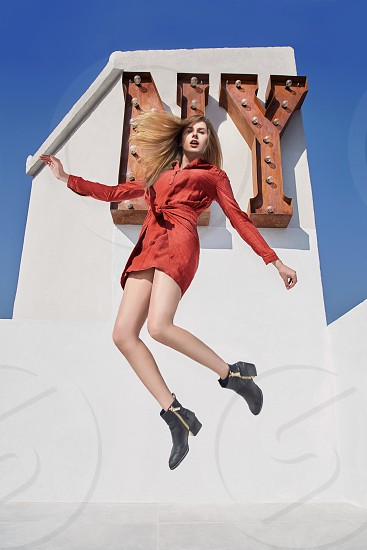 A blonde model jumps in front of a NY sign on the terrace of a building located in Mexico City as part of a fashion shoot photo