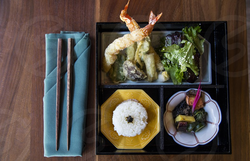 cooked rice beside tempura with leafy greens in bento near brown wooden chopping stick photo
