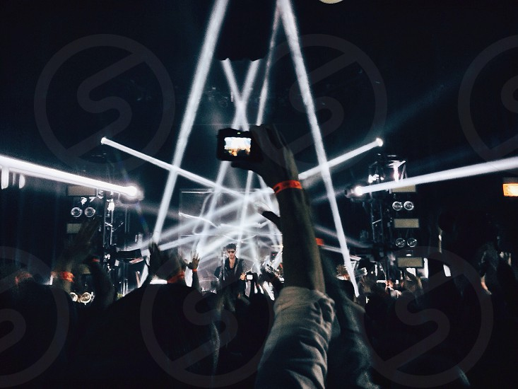 man holding point and shoot digital camera taking a picture in a concert photo