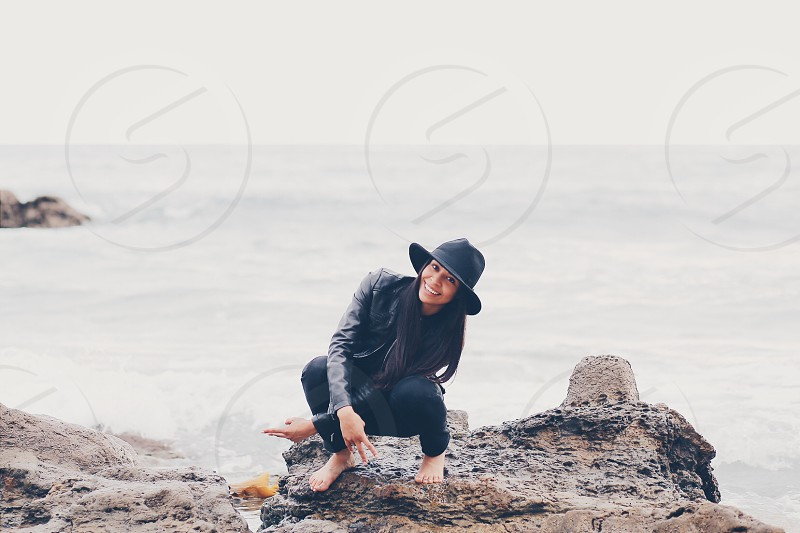 woman in black summer hat black leather jacket and black leggings taking picture in squat position behind ocean during daytime photo