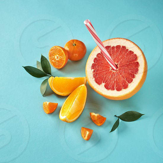 Top view of tropical exotic citrus fruits half a grapefruit tangerines orange slices with a plastic straw for juice on a blue paper background. photo