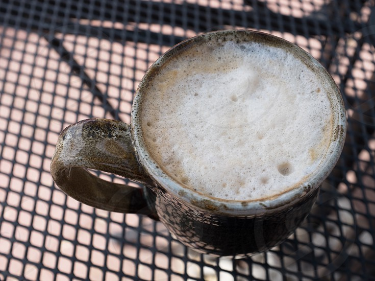 brown ceramic cup filled with foam photo